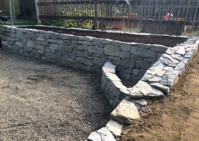 Basalt garden bed with fire pit in corner